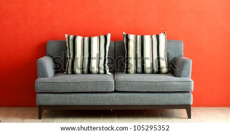 gray sofa put on red stucco background - stock photo