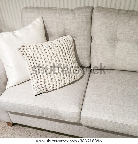 Gray sofa with knitted cushion. Modern style furniture. - stock photo