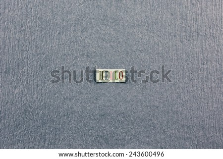 """Gray textured paper with a paper tag reading """"HELLO"""" in multicolored letters.  - stock photo"""
