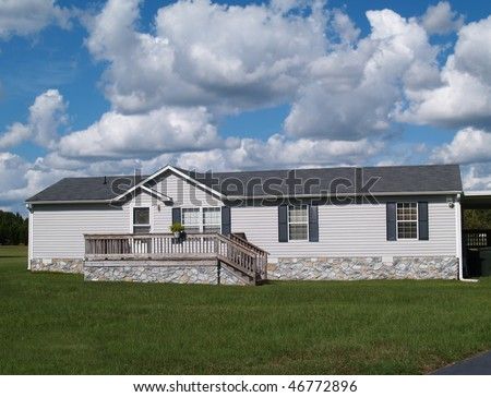 Gray trailer home with stone foundation or skirting and shutters in front of a beautiful sky. - stock photo