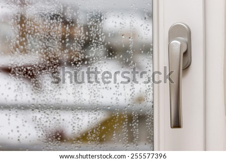 Gray window handle with water droplets on the window in a cold and rainy day outside. - stock photo