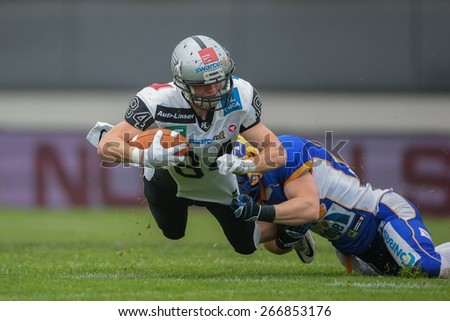GRAZ, AUSTRIA - APRIL 26, 2014: WR Clemens Erlsbacher (#84 Raiders) is tackled by DB Johannes Winter (#25 Giants). - stock photo