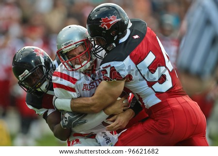 GRAZ, AUSTRIA - JULY 11 QB Christoph Gross (#8 Austria) is tackled by LB Anthony Maggiacomo (#54 Canada) at the Football World Championship on July 11, 2011 in Graz, Austria. - stock photo