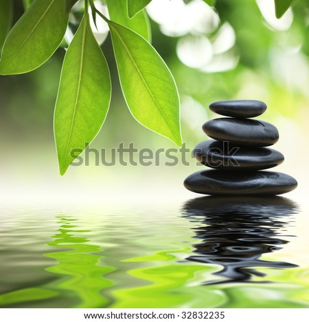 Grean leaves over zen stones pyramid on water surface - stock photo