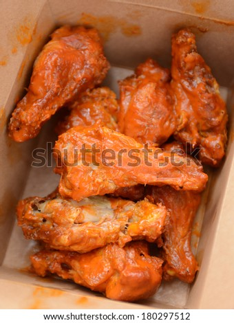 greasy buffalo chicken wings in takeout container - stock photo