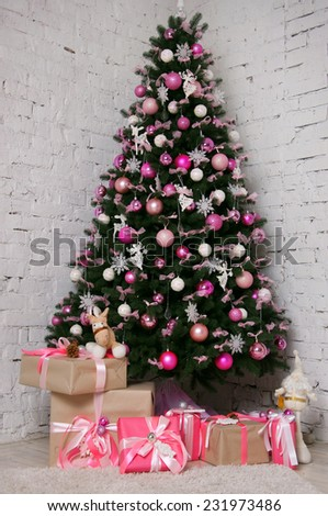 Great beautifully decorated Christmas tree with pink baubles, ribbons, snowflakes, and a lot of gift boxes and toys beneath. Over white brick background - stock photo