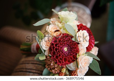Great bridal bouquet of roses, peonies, dahlias, asters and dried flowers. Gold wedding rings on a bouquet - stock photo