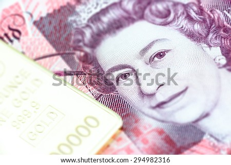 Great Britain fifty pounds notes, a macro close-up with gold bullion - stock photo