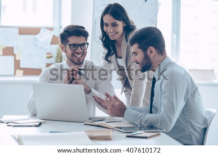 Great business meeting.  Three coworkers discussing something with smile while sitting at the office  - stock photo