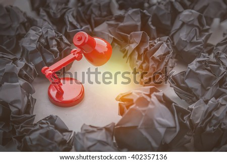 great concept with crumpled office paper and lamp standing on the table - stock photo