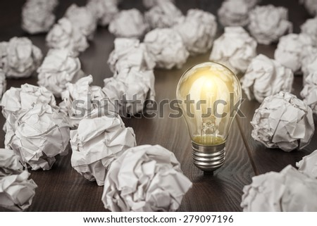 great concept with crumpled office paper and light bulb standing on the table - stock photo