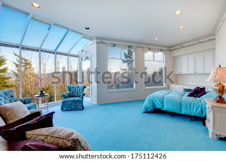 Great design for bedroom with glass wall. Blue carpet floor well matched with light blue bedding and white wood storage cabinets - stock photo