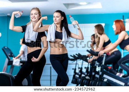 Great fitness workout in the gym. Two friends are athletes in the gym and show their muscles while their friends do sports and pedaling on a stationary bike - stock photo