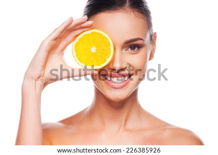 Great food for a healthy lifestyle. Beautiful young shirtless woman holding piece of orange in front of her eye while standing against white background
