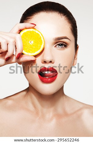 Great food for a healthy lifestyle. Beautiful young shirtless woman with red lips and manicure holding piece of orange in front of her eye while standing against white background - stock photo