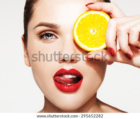 Great food for a healthy lifestyle. Beautiful young shirtless woman with red lips and manicure holding piece of orange in front of her eye while standing against white  - stock photo