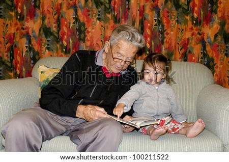 Great Grandad reads a book to his great grandchild on a coach. Concept photo of grandparents, grandfather, grandad,grandchild, childhood, granddaughter, relationship, lifestyle,family, education.