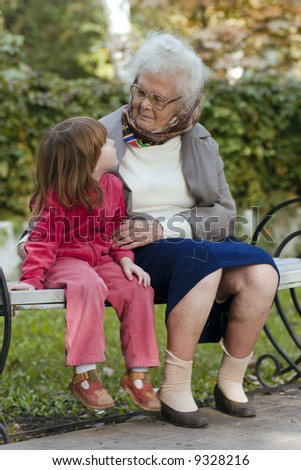 Great grandmother and child sitting on a bench in the park and looking at each other - stock photo