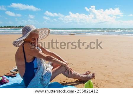Great grandmother having fun at the beach - stock photo