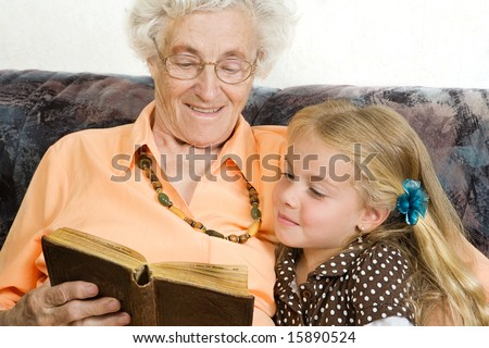 great grandmother is reading her great-granddaughter a story - stock photo