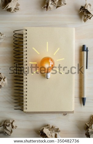 great idea concept with crumpled paper and light bulb on wooden table - stock photo