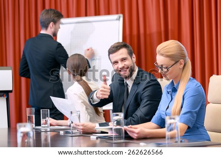 Great job. Businessman in classical black suit paints a chart on the flipchart while his female colleagues turned around to see his picture and his male partner smiles and shows his thumb up - stock photo