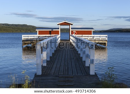 GREAT-LAKE, SWEDEN ON JULY 05. View of a bridge on July 05, 2016 by the Great-Lake, Sweden. Red and white wooden bridge, forest and ridges in the background