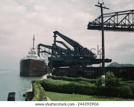 Great Lakes freighter unloading iron ore at the Pennsylvania Railroad ore docks in Cleveland Ohio. One 'Hulett' unloader is lowering its bucket into ship's hold, another loads a railroad car. 1943.
