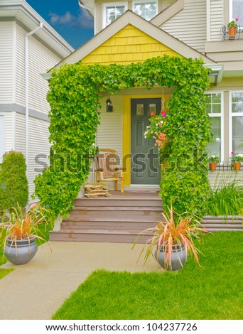 Great looking house entrance with ivy around the columns and hand made chair on the porch - stock photo