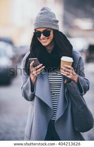 Great message from friend. Beautiful young woman in sunglasses using her smart phone with smile while walking outdoors - stock photo