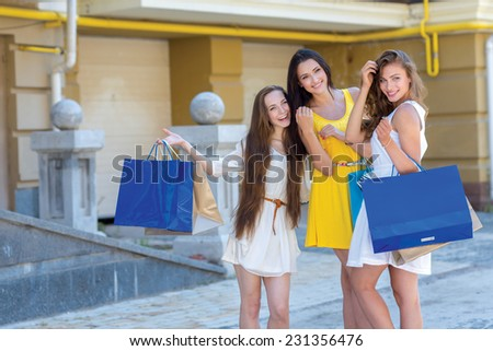 Great mood while shopping. Three great looking pretty girls are holding the shopping bags and having fun after going shopping