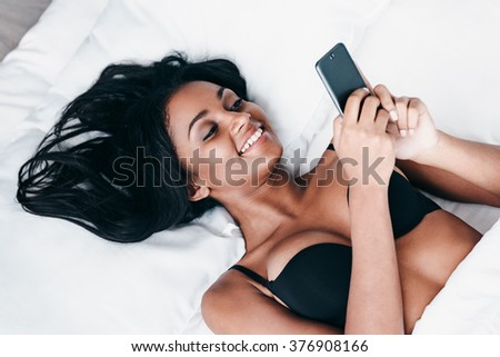 Great morning message. Top view of beautiful young African woman in black lingerie lying in bed and using her smart phone - stock photo