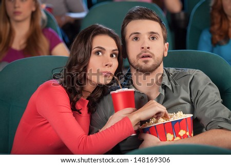 Great movie! Young couple eating popcorn and drinking soda while watching movie at the cinema - stock photo