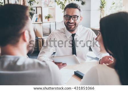 Great news for you! Cheerful mature man in shirt and tie holding digital tablet and gesturing while young couple sitting in front of him at the desk  - stock photo