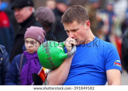 GREAT NOVGOROD, RUSSIA-13 March, 2016 :The male volunteer from the crowd is competing in kettlebell lifting.Traditional folk fun folk holiday Maslenitsa in Great Novgorod,Russia  on March 13,2016.