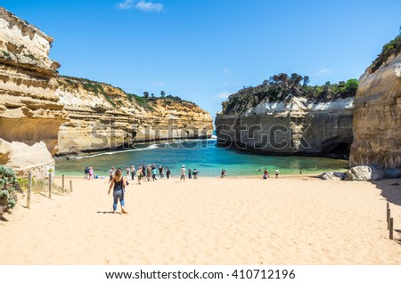 Great Ocean Road, Australia - January 25, 2016: tourists frolicking on a sandy beach at Loch Ard Gorge, a popular tourism destination on the Great Ocean Road.