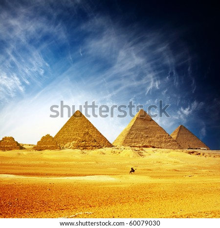 Great pyramids in Giza valley and rider on camel. Egypt - stock photo