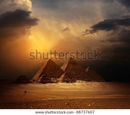 Great pyramids in Giza valley with yellow dark clouds on the background - stock photo