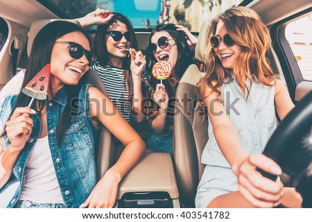 Great start of their journey. Four beautiful young cheerful women looking at each other with smile and holding lollipops while sitting in car - stock photo