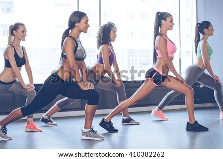 Great stretching. Side view of beautiful cheerful young women with perfect bodies in sportswear doing stretching with smile while standing in front of window at gym - stock photo