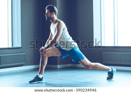 Great stretching. Side view of young handsome man in sportswear doing stretching at gym - stock photo