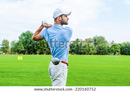 Great strike. Side view of confident golfer swinging his driver and looking away while standing on golf course - stock photo