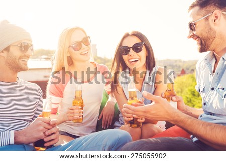 Great time with friends. Four young cheerful people chatting and drinking beer while sitting at the bean bags on the roof of the building - stock photo