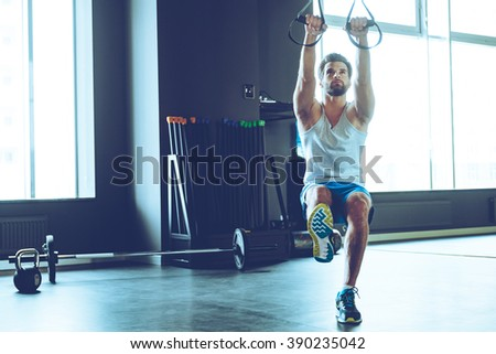 Great TRX workout. Full length of young handsome man in sportswear exercising at gym - stock photo