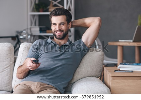 Great TV show.Handsome cheerful young man holding remote control and watching TV while sitting on the couch at home - stock photo