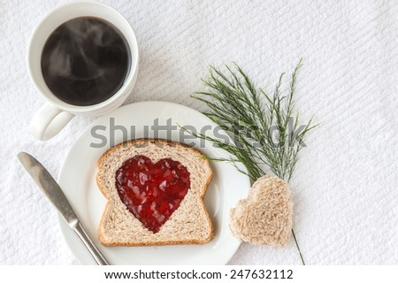 great valentine's day image of a whole wheat slice of bread with a heart shaped hole in the middle filled with red jam in a white plate with a hot cup of coffee on a white background. - stock photo