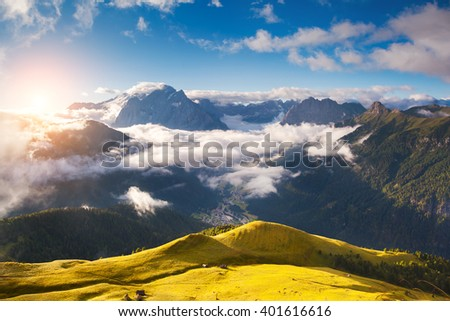 Great view of the foggy Val di Fassa valley. National Park Dolomites (Dolomiti), pass Sella. Location famous resort Canazei, Tyrol, Alp, Italy, Europe. Dramatic and picturesque scene. Beauty world. - stock photo