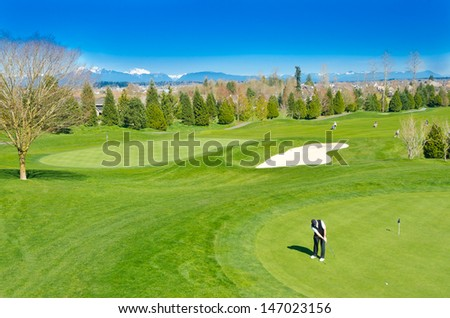Great view (panorama, outlook ) at the beautiful golf course with the mountains at the back. - stock photo