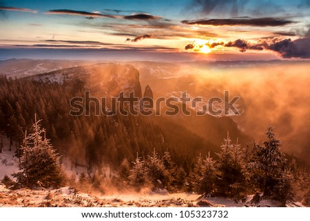 Great winter sunset landscape mountain, with trees, wood, snow, sun, cloud and fog - stock photo