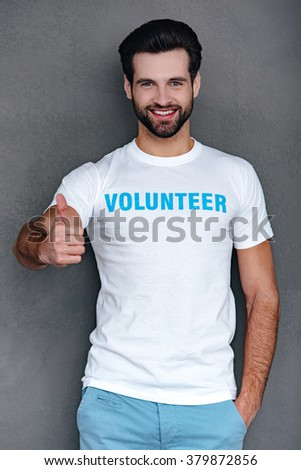 Great work! Confident young man in volunteer t-shirt gesturing thumb up and looking at camera with smile while standing against grey background